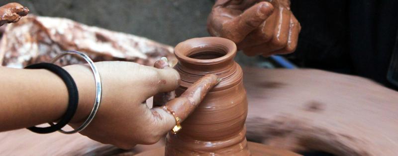 Due persone lavorano la ceramica creando un vaso