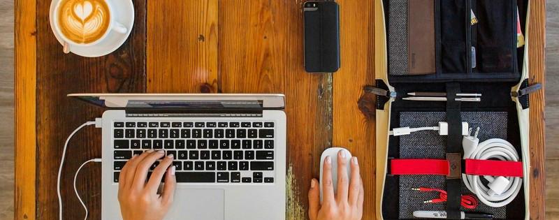Ragazza che scrive al computer davanti a un cappuccino