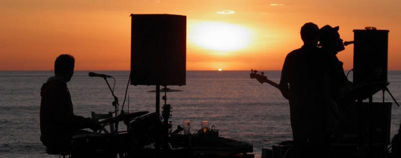 Una band che suona sulla spiaggia al tramonto