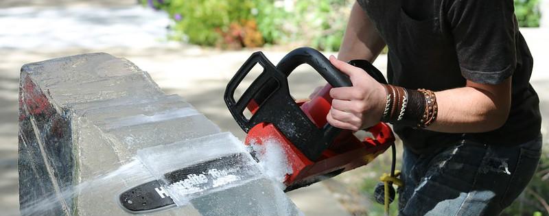 Lavoratore che taglia il ghiaccio con una motosega