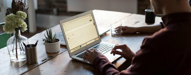 Persona seduta alla scrivania che digita al computer