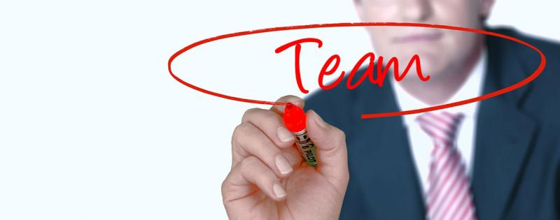 Uomo disegna su una lavagna trasparente la parola Team cerchiata