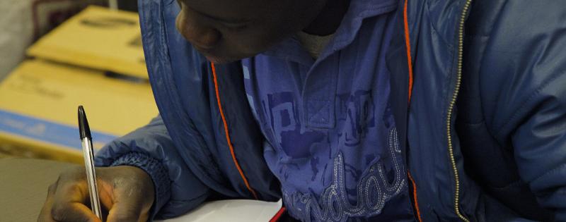 Ragazzo di colore che compila un documento