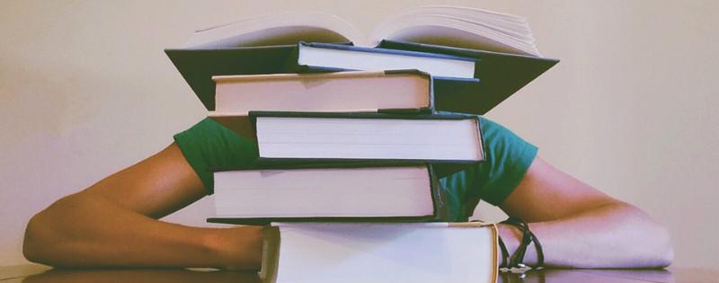 Ragazza sommersa da libri