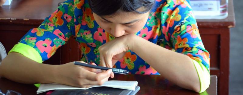 Studentessa con lineamenti asiatici che prende appunti durante una lezione