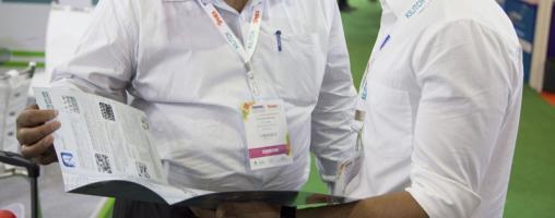 Due persone con cartelle cartacee discutono all'interno di uno spazio di fiera