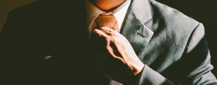 Persona con vestito elegante si stringe la cravatta