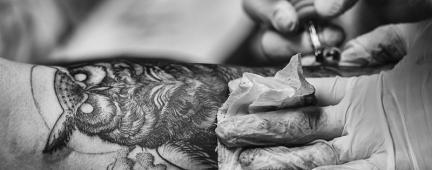 Tatuatore tatua un gufo sul braccio di una persona