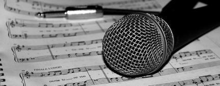 Microfono su spartito musicale in bianco e nero