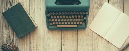 Scrivania con macchina da scrivere, quaderno e fogli