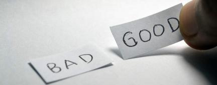 """Su un tavolo ci sono due biglietti con scritto """"Bad"""" e """"Good"""", una persona prende il biglietto """"Good"""""""