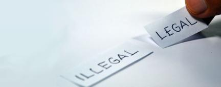 Una mano indica due pezzi di carta con scritto 'Illegal' e 'Legal'
