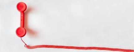 Cornetta di telefono rossa su sfondo bianco