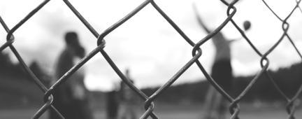 Rete di ferro e nello sfondo ragazzi che giocano a tennis