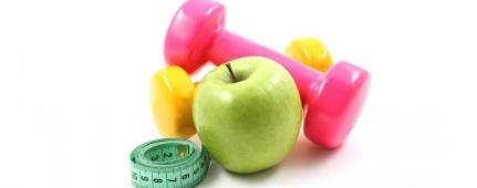Una mela verde con vicino alcuni pesi colorati e un metro da sartoria