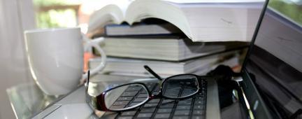 Pc, occhiali, libri e una tazza