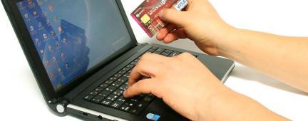 Persona al pc con una carta di credito in mano