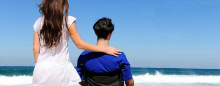 Ragazza e ragazzo in sedia a rotelle guardano il mare all'orizzonte