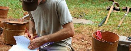 Uomo che scrive su un block notes con accanto un secchio e una zappa